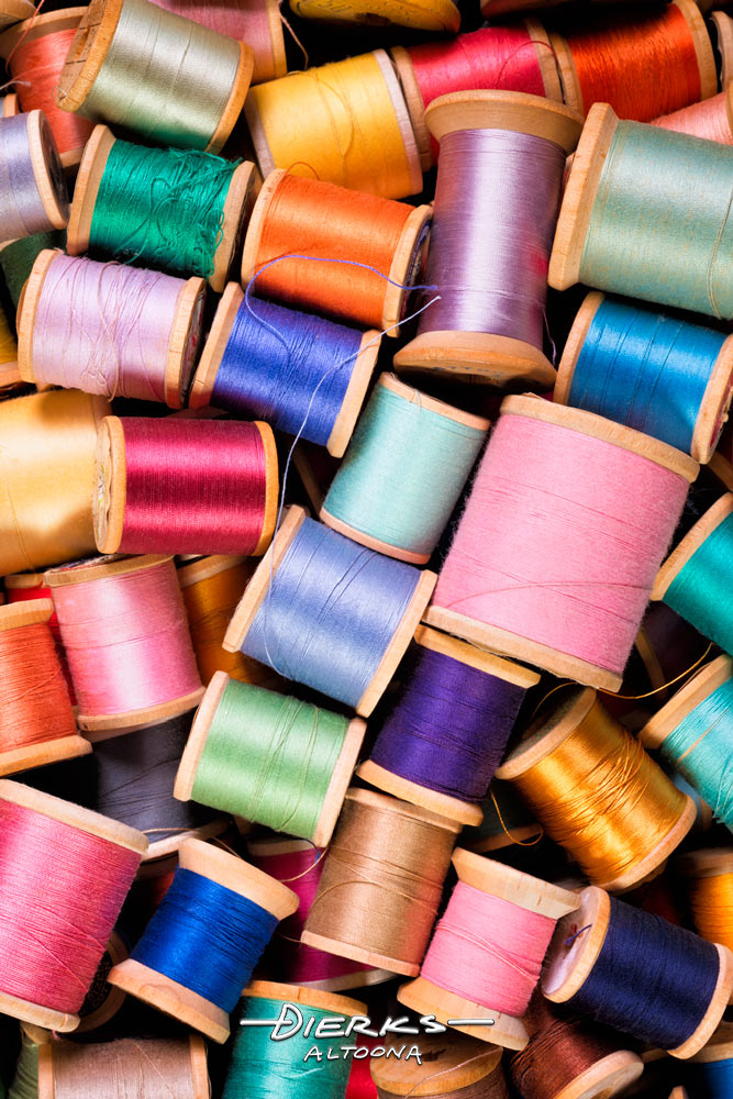 Old wooden spools of sewing thread in many vibrant colors.