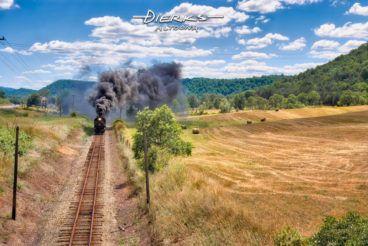An East Broad Top Railroad steam train moves across its home landscape in central Pennsylvania, as the black coal smoke drifts across freshly cut hay fields and into the mountains.
