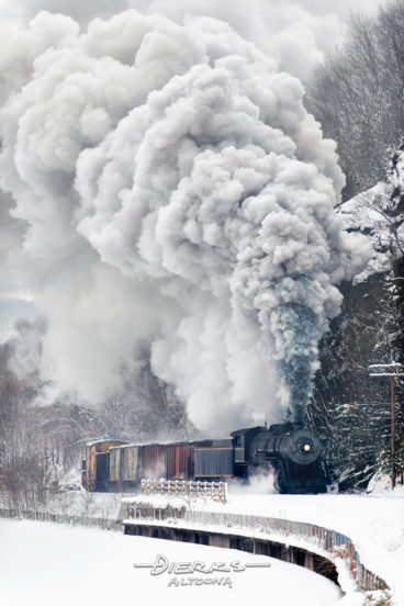 A steam freight train rounding a curve through a snowy rock cut beside a river with steam locomotive billowing smoke in the cold winter air. Taken along Wills Creek in the Cumberland Narrows outside Cumberland, Maryland.