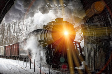 With headlight shining yellow into the darkness, an old fashioned steam train enters a mountain railroad tunnel as the locomotive smoke boils against the ceiling. Lens flares fly all through the shot.