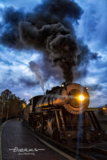 Pushing black smoke, a steam locomotive in excursion service waits to leave the Cumberland MD station in the cool blue light just before dawn.