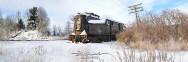 A Pennsylvania Railroad GG1 electric locomotive sits stranded and abandoned in the cold winter snow and twenty below temps.