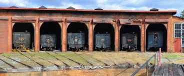 Steam engines lined up at rest in their roundhouse berths with doors open at the East Broad Top Railroad in central Pennsylvania.