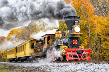 A reproduction antique steam train against fall foliage, an 1860's period locomotive and passenger cars built to recreate President Lincoln's funeral train.
