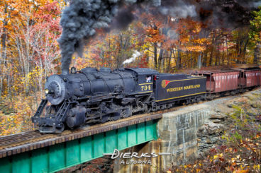 An old railroad steam locomotive pushing thick black coal smoke pulls upgrade in the Maryland mountains with a train of vintage freight cars. A few miles back, Western Maryland #734 left the station in Cumberland MD with a train of vintage freight cars, hauling them straight out of the past into the now.