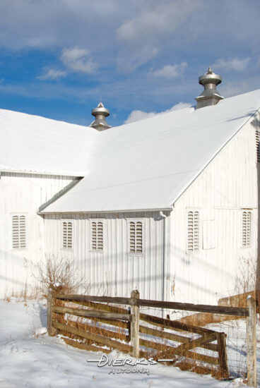 Ona sunny winter day in the country, a white barn roof is covered in new white snow.