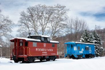 A Pennsylvania Railroad N5 cabin car and a blue Conrail caboose on display in new winter snow at Tyrone, PA.
