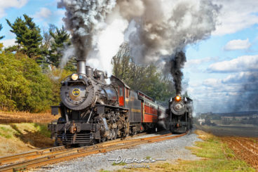 On the Strasburg Railroad, a steam locomotive pulls a passenger train past another steam train sitting in a passing siding.
