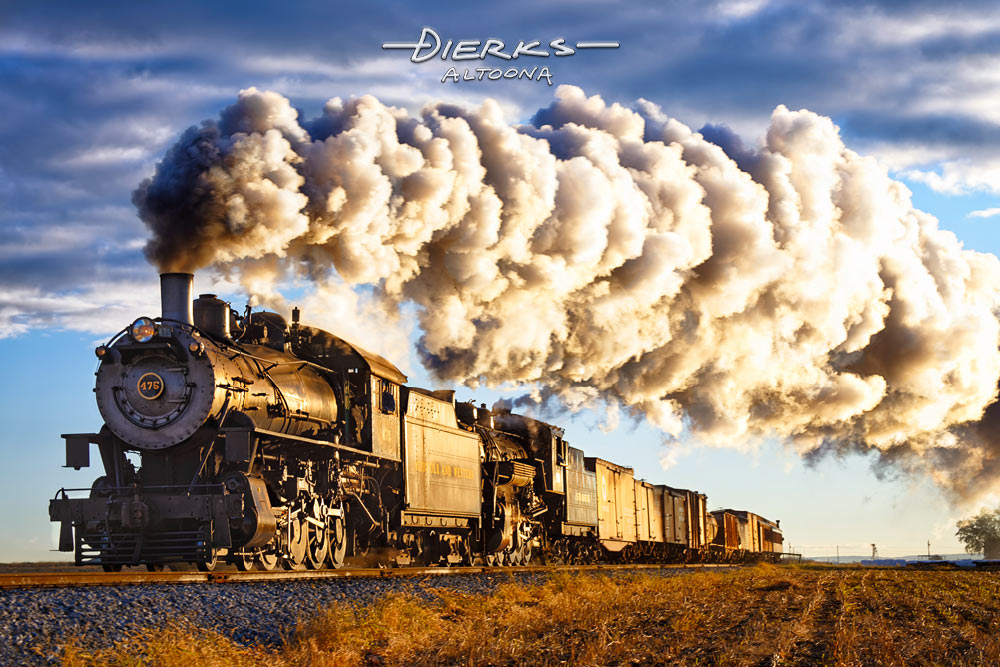 The first yellow light of dawn hits the side of two double-heading Strasburg Railroad locomotives moving through the Amish farmland.
