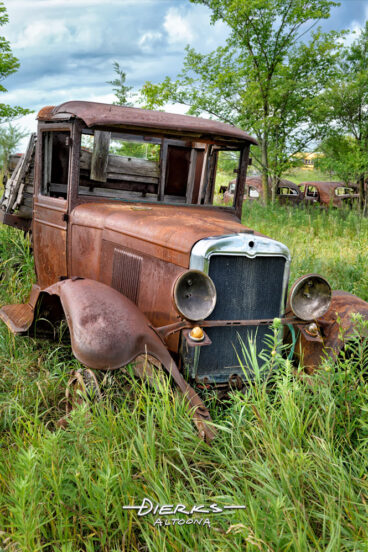 An old and rusty rum runner truck in junkyard high grass, Ford Model AA truck.