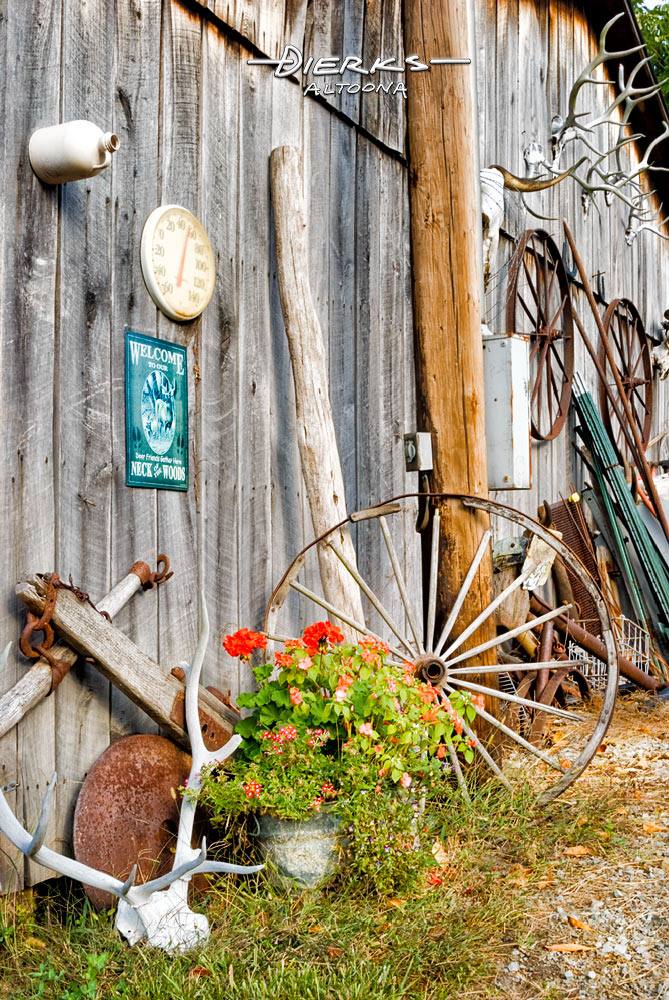 A rustic hodge podge collection of Americana outside a weathered gray barn, including elk antlers and wagon wheels.
