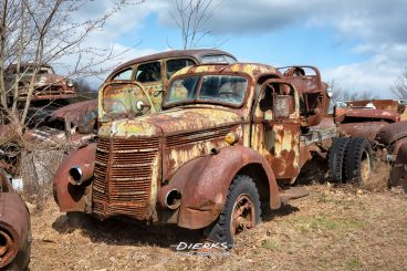 A 1938 International Harvester heavy duty truck with dual wheels rusts away in the bright sun of an old school junkyard.