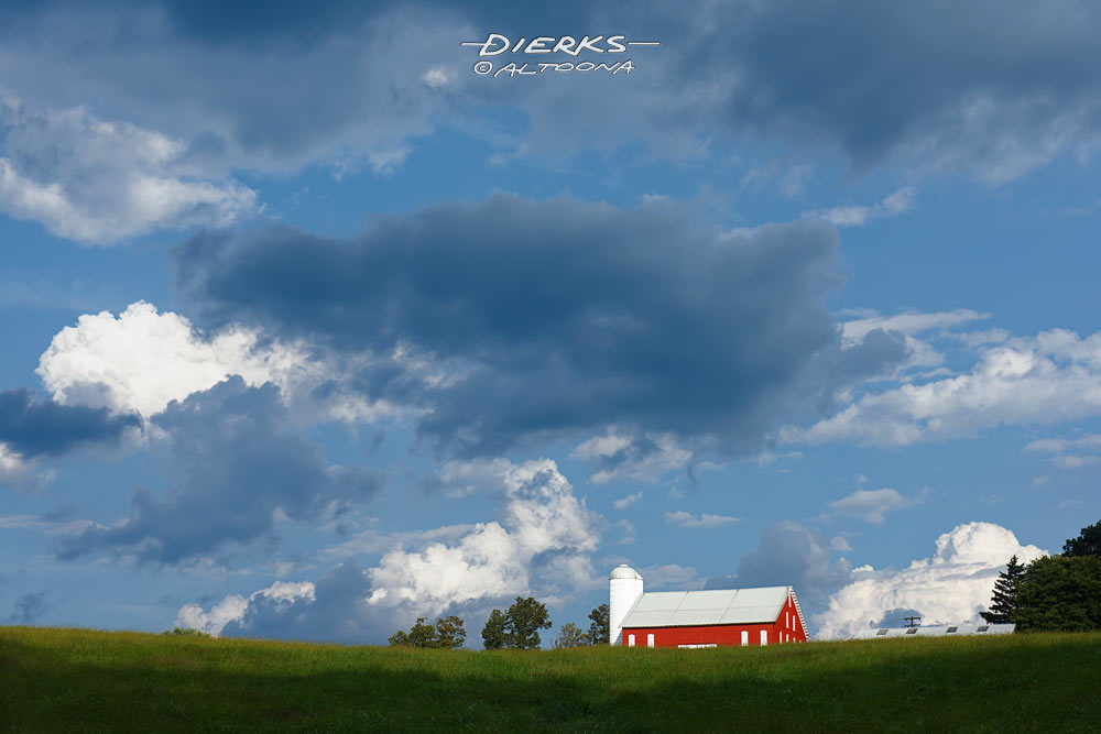 On a hot summer day, a big sky filled with white and blue clouds over a red barn and a green farm field of grass.