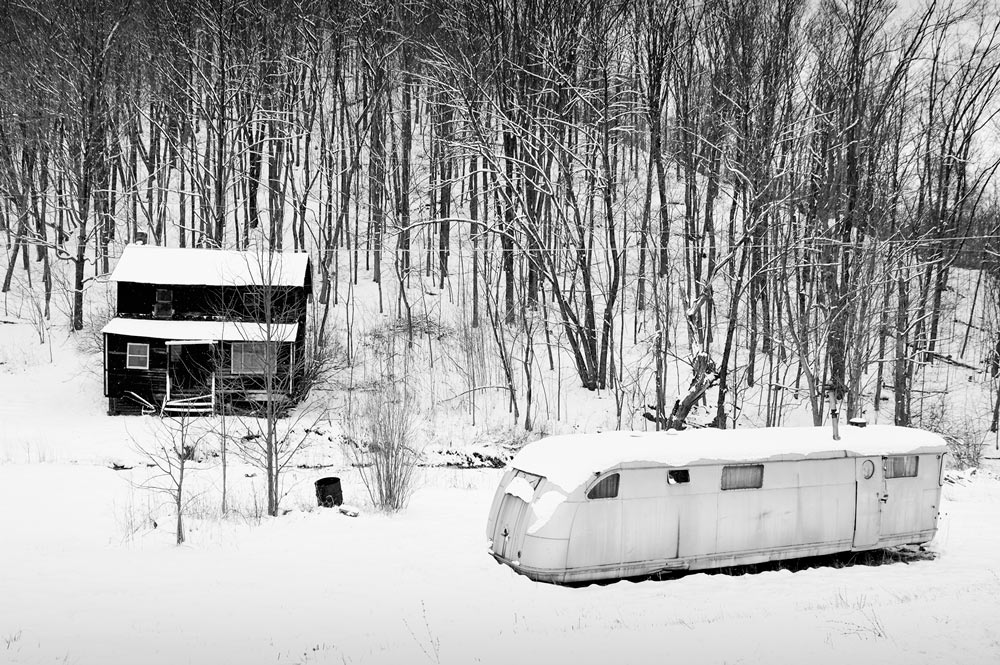 An abandoned shack house across from an empty old streamliner house trailer out in hillbilly country in winter.